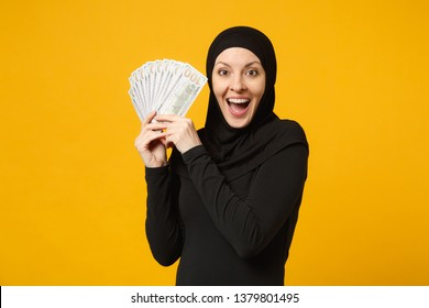 Young arabian muslim woman in hijab black clothes hold fan of cash money in dollar banknotes isolated on yellow wall background studio portrait. People religious lifestyle concept. Mock up copy space