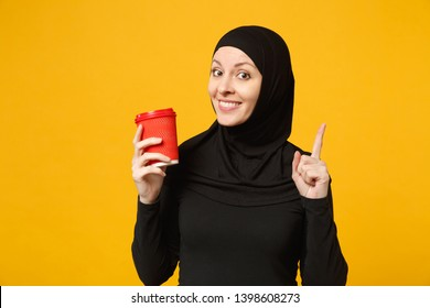Young arabian muslim woman in hijab black clothes hold paper cup of coffee isolated on yellow wall background, studio portrait. People religious lifestyle concept. Mock up copy space