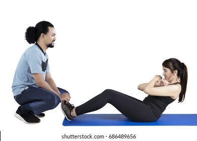 Young Arabian woman doing sit-up with her personal trainer in the studio, isolated on white background