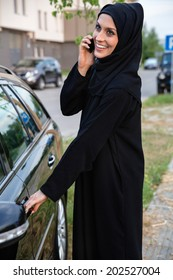 Young Arabian Woman Getting In The Car While Speaking On Smart Phone