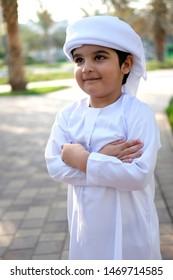 Young Arabic boy arms closed while wearing cultural ethnic Emirati Kandura dress
