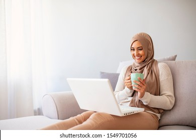 Young Arabic female entrepreneur wearing a hijab working on a laptop and drinking coffee while sitting at living room. Muslim woman with laptop at home.  Attractive young woman in head scraf