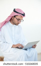 Young Arabic man in office with laptop