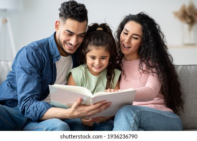 Young Arabic Parents Reading Book With Their Cute Little Daughter At Home