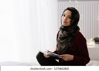 Young arabic woman in hijab reading a book in bedroom
