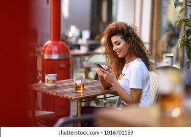 Young arabic woman smiling and sitting in an urban bar in the street looking at her smartphone. Arab girl in casual clothes drinking a soda outdoors.