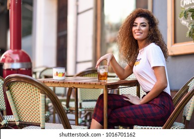 Young arabic woman smiling and sitting in an urban bar in the street. Arab girl in casual clothes drinking a soda outdoors.