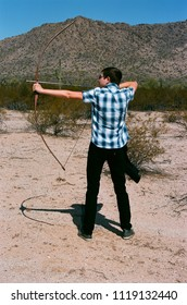Young archer shooting a traditional long bow and arrow