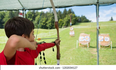 Young archery kid outdoors.