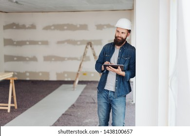 Young architect consulting online on a tablet as he stands in an unfinished room on site leaning against the wall thinking