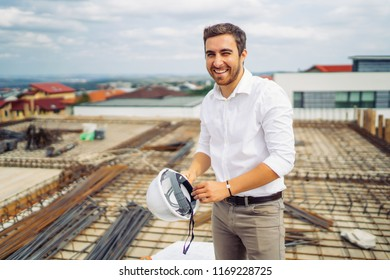 young architect engineer working and smiling on construction with hardhat in hand