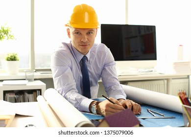 Young Architect Freelance Man Working on Blueprint. Businessman in Helmet Sitting at Office Desk making Building Plans Construction. Project Engineer Expert Specialist Qualified Job Occupation