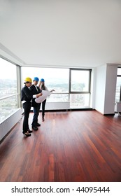 young architect group in big bright modern new apartment looking blueprints and building plans
