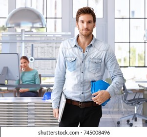 Young architect leaving office carrying hardhat and laptop.