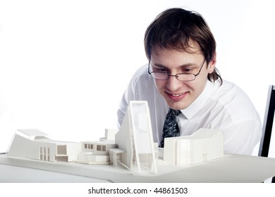young architect looking at architectural model