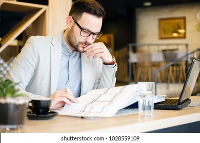 Young architect looking over building plans while working in a modern cafe.