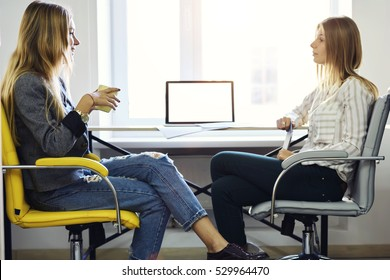 Young architect student being interviewed for job in design company,having conversations about successful startup concept with cup of tea sitting in coworking with wifi and laptop blank mock up screen