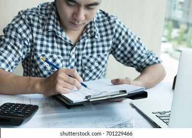 young architect working on real estate project at workplace. Male engineer hand working with living house blueprint at office. Business, people, construction and building concept
