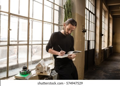 Young architect is writing or drawing on his notebook in the old industrial space with big factory windows. Man is sitting in front of window and holding the sketch book. Color toned image.