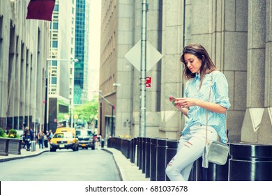 Young Argentine Woman wearing light blue striped shirt, white destroyed jeans, shoulder carrying small bag, sitting on street in New York, looking down, texting on cell phone. Cars on background.