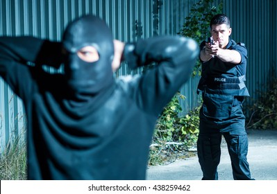 Young armed policeman pointing a gun at a masked thief who is holding his hands on his head