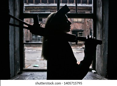Young armed survivalist woman silhouette with ak rifle on her shoulder with apocalyptic war area around her