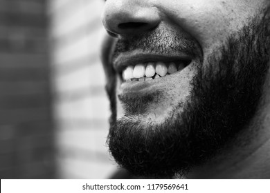 young Armenian guy with a thick beard smiles and shows straight teeth. concept: birthday card for barbershop and a dental clinic. brutal guy posing near a brick wall