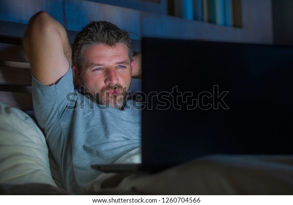 young aroused man alone in bed playing cybersex using laptop computer watching porn sex movie late at night with lascivious pervert face expression in internet pornographic sexual content