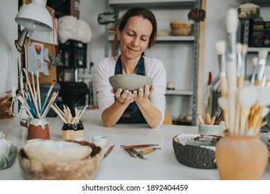 young artisan woman working with her hand a piece of ceramic