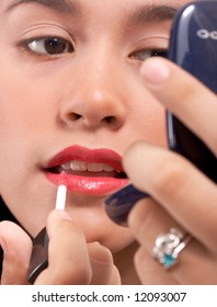 young artist applying a red color lipstick