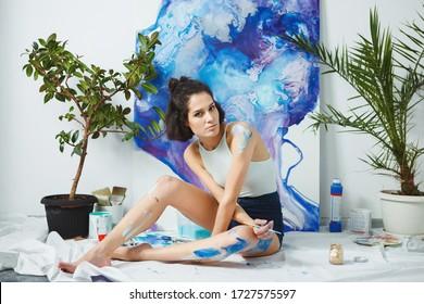 Un jeune artiste crée de nouvelles oeuvres d'art à même le sol. Femme sérieuse