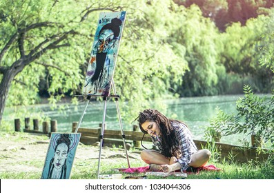Young artist girl drawing draft in park near lake - Painter woman with dreadlocks hairstyle working on her art in the nature outdoor - Concept of people expressing arts