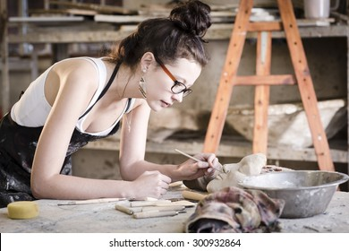 young artist moulding raw clay in art studio