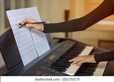 young artist musician woman practices and trains skills, compose writing notes by pencil. Teaching student to play the piano in music room.
