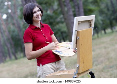 Young artist is painting outdoors