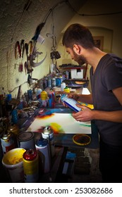 Young artist working in his studio creating artwork using spray paint.