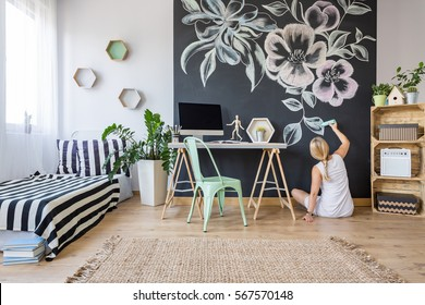 Young artistic woman painting flowers on a black board in her bedroom
