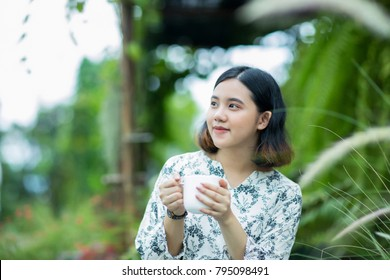 Young asain girl holding a cup of coffee in the garden