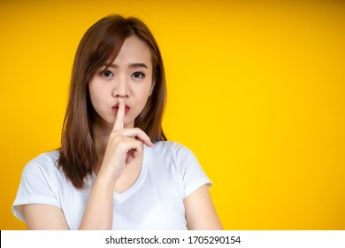 Young Asain woman requires silence. Young beautiful brunette has put forefinger to lips as sign of silence, isolated on yellow
