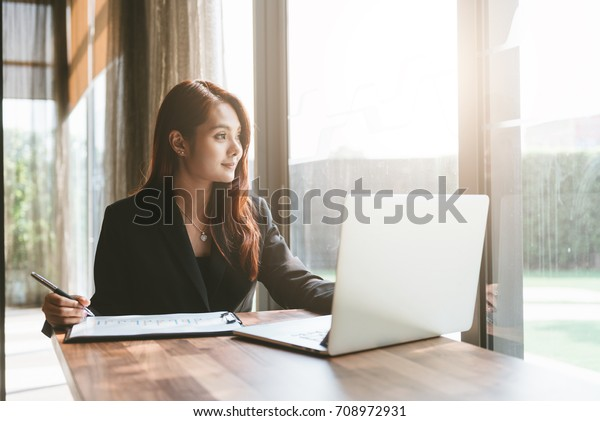 Young asia business woman working with laptop in office space