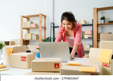 Young Asia entrepreneur businesswoman check product purchase order on stock and save to computer laptop work at home office. Small business owner, online market delivery, lifestyle freelance concept.