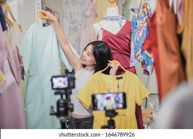 Young Asia girl selling clothes online by live streaming. selling it online live streaming Concept