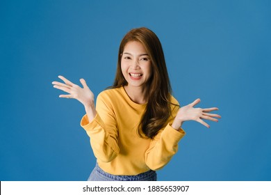 Young Asia lady feeling happiness with positive expression, joyful and exciting, dressed in casual cloth and looking at camera isolated on blue background. Happy adorable glad woman rejoices success.
