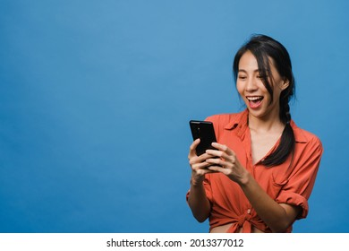 Young Asia lady using phone with positive expression, smiles broadly, dressed in casual clothing feeling happiness and stand isolated on blue background. Happy adorable glad woman rejoices success. - Shutterstock ID 2013377012