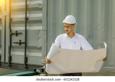 Young Asia man engineer wearing safety white helmet in white shirt checking construction site building.