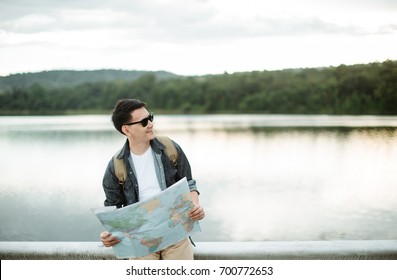Young Asia man as he reads the map, traveling alone
