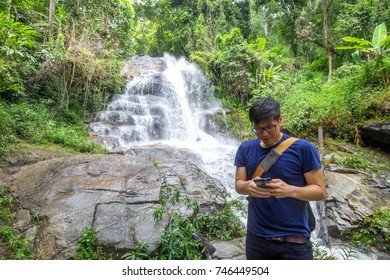 cde58b5e987 A young asia tourism man Standing in front of beautiful waterfall in the  forest.Happy