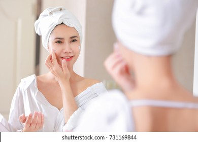 Young asia woman applying foundation or moisturizer on her face in front of mirror.