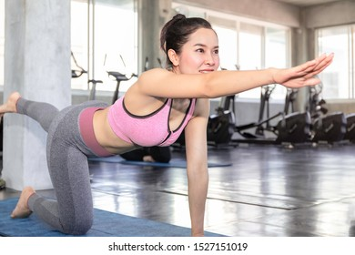 Young Asia woman practicing yoga with sportswear bra and pants at fitness gym.