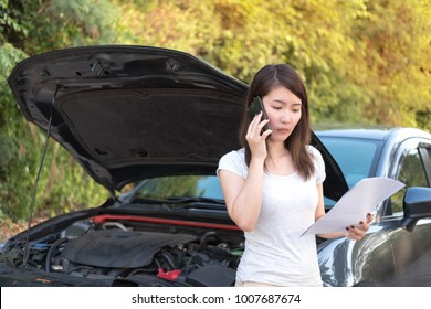 Young asia woman sitting in front of her car, try to calling for assistance with her car broken down